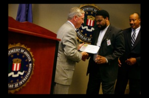 "Photograph by Callie Shell/Aurora for Time ""Imam in America."" Imam Mohamed Magid receives a plaque of appreciation during a meeting at the F.B.I. for the Arab, Muslim and Sikh Advisory Council. Imam Magid often works with the F.B.I. Washington, DC. 09.20.2005."